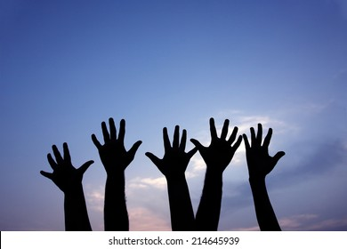 volunteer group raising hands against blue sky background