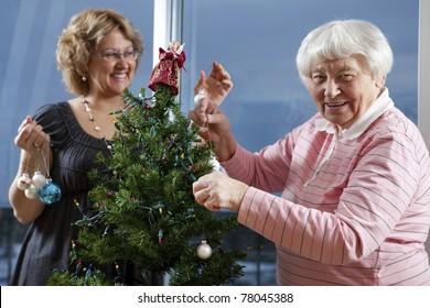 Volunteer helping senior decorate her Christmas Tree