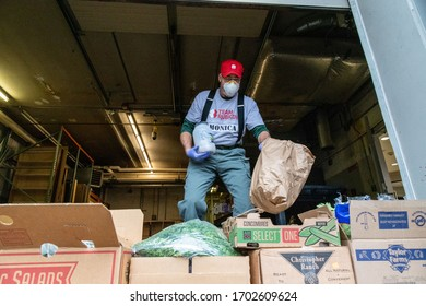 A volunteer helps transfer perishable food from the Cincinnati Art Museum to local food banks in the wake of the coronavirus pandemic, Thursday, March 19, 2020, in Cincinnati. (Photo by Jason Whitman)