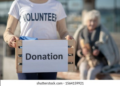 Volunteer holding box. Close up of young kind volunteer holding box with donation for homeless people