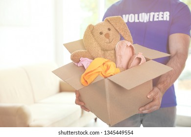 Volunteer holding box with donations indoors. Space for text