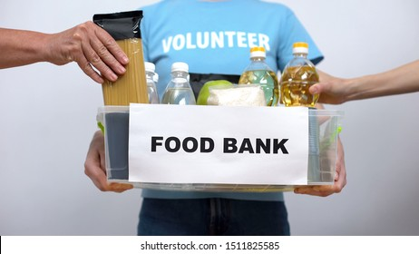 Volunteer holding food bank container, hands putting provision in box, help