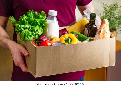 Volunteer holding food in a donation cardboard box with various food. Open cardboard box with oil, vegetables, milk, canned food, cereals and pasta. Food delivery concept with copy space.