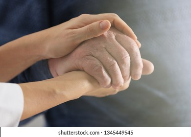 Volunteer holding hand of senior man, closeup