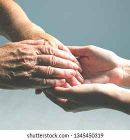 Volunteer holding hand of senior woman against light background, closeup