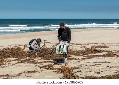 Volunteer keeping plastic waste out from Furadouro beach in Ovar, Portugal. Environmental pollution. Conservation, friendship.
