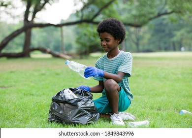 Volunteer kid. African American boy in gloves picking up plastic bottles into a black garbage bag outdoor. Volunteer and charity concept