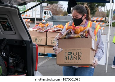 A volunteer loads food into the trunk of a vehicle during a drive thru food distribution by the Los Angeles Regional Food Bank in Glendora, Calif. Dce. 8, 2020.