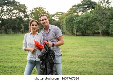 Volunteer lovers couple wearing gloves walking to collect rubbish in the park To keep the environment clean