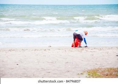volunteer man cleaning on beach