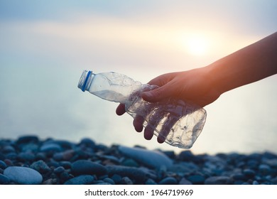 Volunteer man and plastic bottle, clean up day, collecting waste on sea beach, pollution and recycling concept