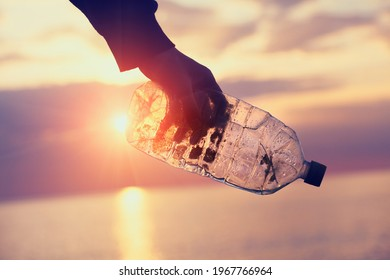 Volunteer man's hand picking up plastic bottle, clean up day, collecting waste on sea beach, pollution and recycling concept