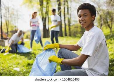 Volunteer opportunities. Attractive male volunteer using garbage bag while staring at camera