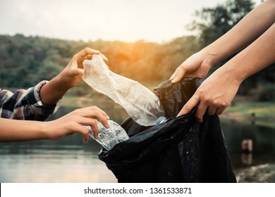 The volunteer picking up a bottle plastic in the river , protect environment from a water pollution concept.