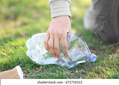 Volunteer picking up litter from grass, closeup