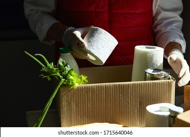 Volunteer in the protective medical mask and gloves putting food In donation box. Delivery man employee in red vest packing box with food. Service quarantine pandemic coronavirus.