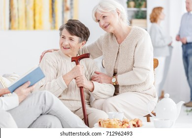Volunteer reading a book to happy elderly woman with a cane and her senior friend at day-care center