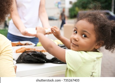 Volunteer sharing food with poor African child outdoors