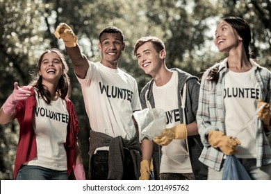 Volunteer sign. Beaming funny students wearing white shirt with volunteer sign feeling responsible while cleaning forest