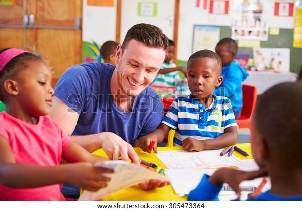 Freiwilligenlehrer, der mit Vorschulkindern im Klassenzimmer sitzt