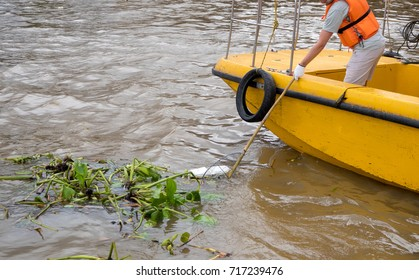 volunteer with team stand on yellow boat gathering garbage on river bank