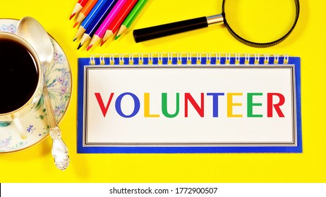 Volunteer — the text label for the notebook planning the event. Engaging in socially useful activities on a gratuitous basis.