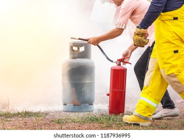Volunteer using fire extinguisher from hose for fire fighting during basic fire fighting training and fire drill evacuation