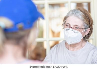 Freiwillige besucht eine ältere Frau, die während der Quarantäneepidemie Coronavirus (Covid-19) Schutzmasken trägt