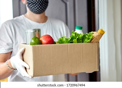 Volunteer in white protective mask and gloves delivery donation box at home. Courier man with packing box with food, contactless delivery. Service quarantine pandemic coronavirus.