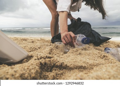 Volunteer woman collecting trash on the beach. Trash-free seas concept. Single-use plastic is a human addiction that is destroying our planet