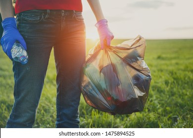 volunteer young woman collecting garbage, holding full bag of waste and plastic bag, land pollution, environmental problem, copy space, sunset light, world environment day