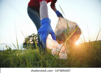 volunteer young woman collecting garbage, picking up waste at sunset light, land pollution, environmental problem