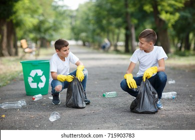 Volunteering, charity, cleaning, people, children and ecology concept - group of happy volunteers with garbage bags walking in park. Outdoors photo. Environmental protection concept.