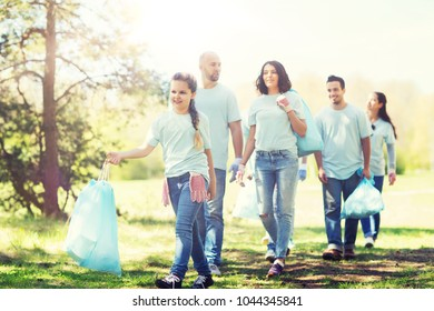 volunteering, charity, cleaning, people and ecology concept - group of happy volunteers with garbage bags walking in park