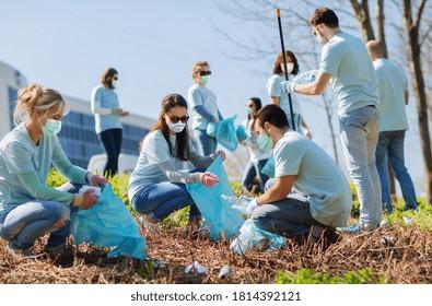 concept du bénévolat, de la charité et de l'écologie - groupe de bénévoles portant un masque médical de protection contre les maladies virales avec sacs à ordures nettoyage zone extérieure