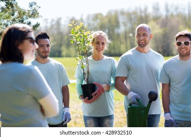 volunteering, charity, gardening, people and ecology concept - group of happy volunteers with tree seedlings and watering can in park