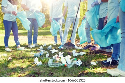 volunteering, charity, people and ecology concept - group of volunteers with garbage bags and rake cleaning area in park