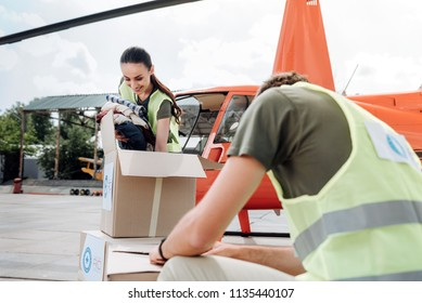 Volunteering foundation. Ambitious two volunteers posing near helicopter and studying boxes