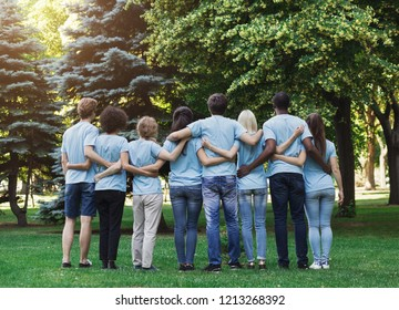 Volunteering, people and ecology concept. Group of volunteers embracing in park, back view, copy space