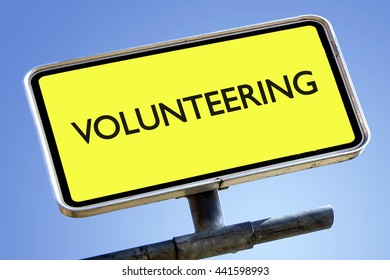 VOLUNTEERING word on roadsign with yellow background