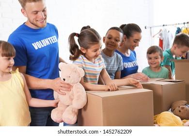 Volunteers with children sorting donation goods indoors