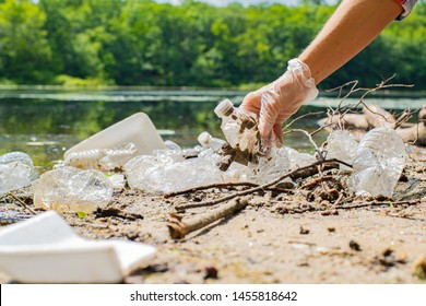 Volunteers cleaning garbage near river. Women picking up a bottle plastic in the lake, pollution and environment. Ecology concept