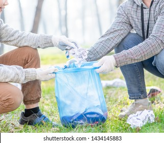 Volunteers collect garbage in plastic bags in a summer park. Volunteer and ecology concept