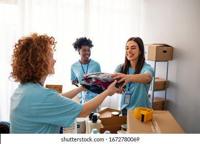Volunteers Collecting Food Donations In Warehouse. Team of volunteers holding donations boxes in a large warehouse. Volunteers putting clothes in donation boxes, social worker making notes charity