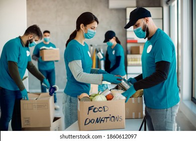 Volunteers cooperating while sorting food in donation boxes for charity food bank.