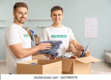 Volunteers with donations for poor people indoors