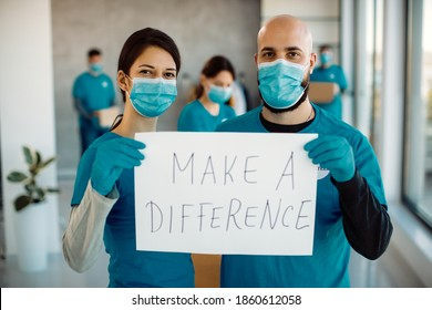 Volunteers with face masks working at charitable foundation and holding a placard with 'make a difference' inscription while looking at camera.