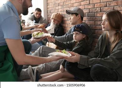 Volunteers giving food to poor people indoors