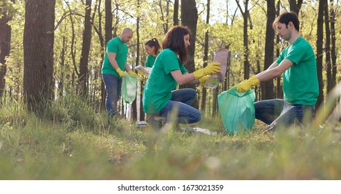 Volunteers in green T-shirts clean up the plastic trash in the park.