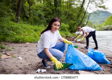 Volunteers on river shore collecting garbage